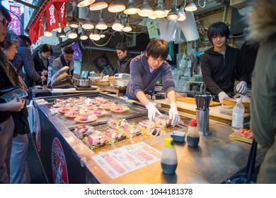 Tokyo, Japan - February 17, 2017: People looking for fresh Sushi and Sashimi set from seller at Tsukiji market.