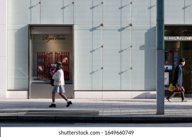 TOKYO, JAPAN -  February 19, 2020: View of a Ginza street with pedestrians in the sunlight and shade passing Matsuya Department store which has a Roger Vivier window display.