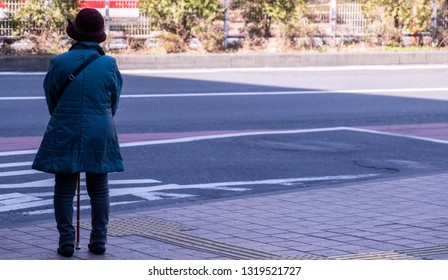TOKYO, JAPAN - FEBRUARY 21ST, 2019. Elderly woman waiting for a bus at a Shibuya bus stop during winter season.