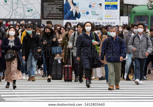 Tokyo, Japan, February 22, 2020 - Pedestrians wearing surgical mask to prevent infectious deseases walk in Shibuya's famous scramble crossing.