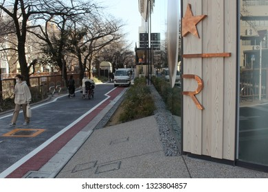 TOKYO, JAPAN - February 23, 2019: View of the side and of the Kengo Kuma-designed Starbucks Reserve Roastery in Tokyo and an adjoining street.