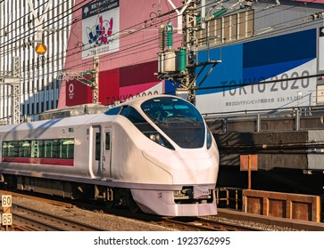 tokyo, japan - february 23 2021: Close up on a E657 series limited express train passing in front of the Tokyo Sports Square building promoting the Tokyo 2020 Olympic Games at Yurakucho station.