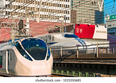 tokyo, japan - february 23 2021: Close up on E657 series limited express train departing from Yurakucho station and 700 series Shinkansen bullet train passing beside the Tokyo Sports Square building.