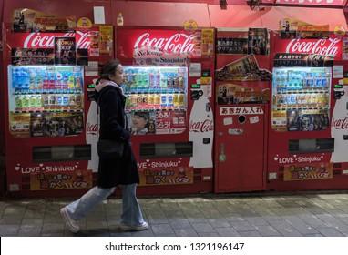 TOKYO, JAPAN - FEBRUARY 23RD, 2019. People walking by Coca Cola vending machines at Kabukicho district sidewalk at night.