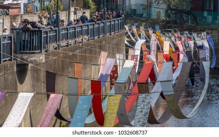 TOKYO, JAPAN - FEBRUARY 24TH 2018. Colourful printed and dyed kimono fabrics hung out to dry in the middle of a river during the Fabric Dyeing Festival in Shinjuku.