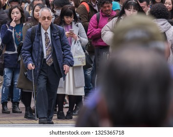 TOKYO, JAPAN - FEBRUARY 27TH, 2019. Old man in business suit crossing the famous Shibuya crosswalk in winter.