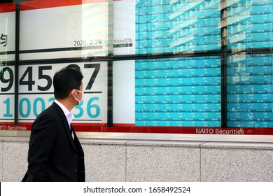 TOKYO, JAPAN - February 28, 2020:  Passerby looks at screen displaying Japanese stock prices at Naito Securities branch on a street in Kayabacho. He is wearing a face mask during coronavirus outbreak.