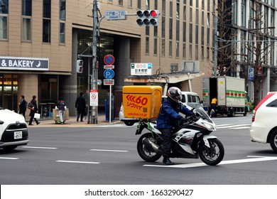 TOKYO, JAPAN - February 28, 2020:  A Sokuhai company dispatch rider in traffic at a junction in central Toyko. A Nihombashi train station entrance and a delivery truck are in the background.