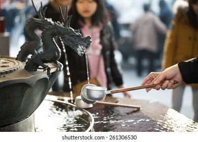 TOKYO, JAPAN - FEBRUARY 3, 2015: unidentified people clean hands and mouth with the water in purification fountain at Sensoji Temple located in Asakusa.