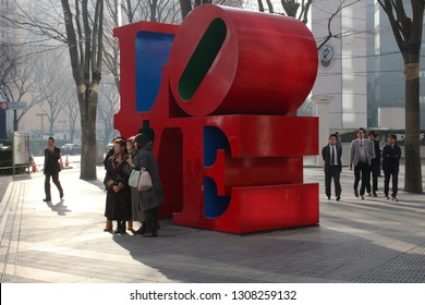 TOKYO, JAPAN - February 7, 2019: A group of visitors have their photo taken in front of a 'Love' sculpture by Robert Indiana installed on a street in Shinjuku on a sunny winter's day.