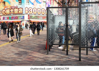 TOKYO, JAPAN - February 7, 2019:  View of a sidewalk and a designated smoking area in Shinjuku. In the background there is a pachinko and slot center.