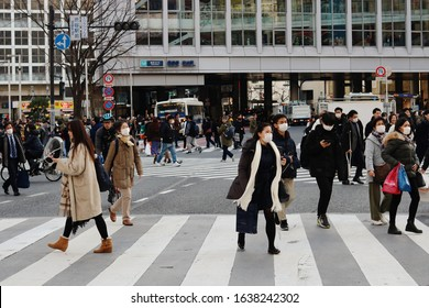 TOKYO, JAPAN - February 7, 2020: Shibuya's large scramble crossing. People are wearing face masks during the coronavirus outbreak. Some motion blur.