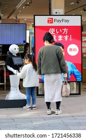 TOKYO, JAPAN - February 8, 2020: A Pepper robot at the front of a Softbank store in Ginza shakes hands with a passerby. The screen is promoting PayPay mobile payment.