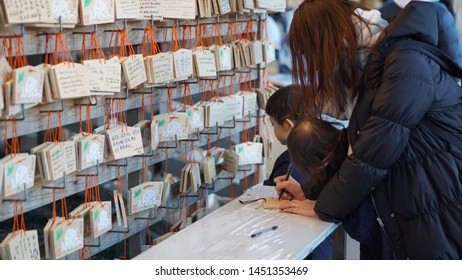 "Tokyo, Japan - Jan 27, 2019: Tourist write their wishes on wood Japanese votive tablets at Meiji-jingu. It s a votive tablet called ""EMA"" at the traditional shrine."