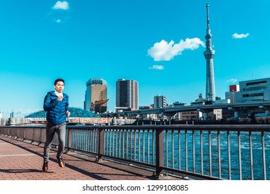 Tokyo, Japan - Jan 9, 2019: Asian man exercise running by Sumida river, Tokyo Skytree in background