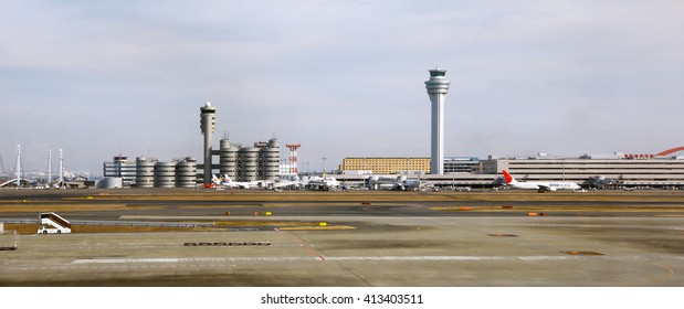 Tokyo, Japan - January 04, 2015: contemporary buildings of Haneda airport. Control tower, runway landing strip and some airplanes are also visible.