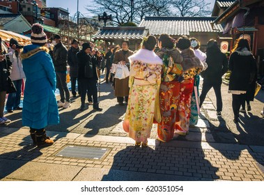 Tokyo, Japan - January 12, 2015:  Girls wearing traditional 'furisode' have their photographs taken by family members to celebrate Coming of Age Day (Seijin No Hi) at Senso-ji temple in Tokyo.