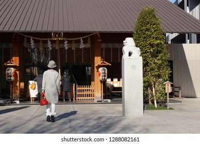 TOKYO, JAPAN - January 17, 2019: The Akagi Shrine in Kagurazaka which was designed by Kengo Kuma.  The building is the shrine's Haiden. A komainu (lion-dog) on a tall plinth is on the right.