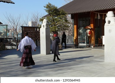 TOKYO, JAPAN - January 17, 2019: A  priest & visitors at Kagurazaka's Kengo Kuma-designed Akagi Shrine. In the background is its Haiden with komainu (lion-dogs) on a tall plinths in front of it.