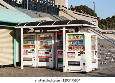 TOKYO, JAPAN - January 17, 2019: A group of drinks vending machines stocked with hot and cold drinks at the Budokan indoor arena where people are waiting in line to enter a rock concert.