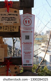 TOKYO, JAPAN - January 17, 2019: A sign at Akagi Shrine in Kagurazaka with a QR code which when scanned provides info on the adjacent Ema, small wooden plaques with prayers or wishes written on them.