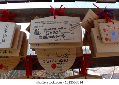 TOKYO, JAPAN - January 17, 2019:  Ema, small wooden plaques with prayers or wishes written on them, attached to a wooded frame at Akagi Shrine in Kagurazaka.