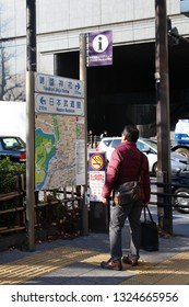 TOKYO, JAPAN - January 17, 2019: A visitor looks at a a street map in Kudanshita with signs above it showing the way to Nippon Budokan and Yasukuni Jinja Shrine.