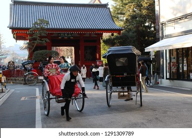 TOKYO, JAPAN - January 19, 2019: Visitors riding in a rickshaw in Asakusa with Nitenmon Gate in the background.