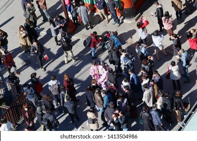 TOKYO, JAPAN - January 19, 2019: Overhead view of visitors, many of whom are taking photos and checking their phones, in front of Asakusa's Kaminarimon.