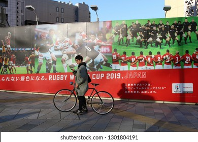 TOKYO, JAPAN - January 27, 2019: A cyclist checks his phone on an Aoyama street corner in front of a billboard advertising the 2019 Rugby World Cup.