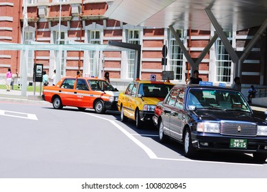 TOKYO, JAPAN - January 4, 2017: Viewed from a public sidewalk, black ,red and yellow taxis wait in front of the classic brick facade of Tokyo Station.