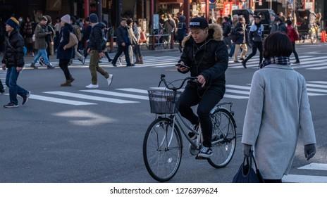 TOKYO, JAPAN - JANUARY 5TH , 2019. Man cycling while looking at his smartphone at In Asakusa street.