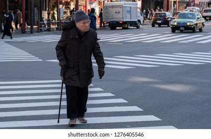 TOKYO, JAPAN - JANUARY 5TH, 2019. Old man waith walking stick crossing the street in Asakusa in the morning.