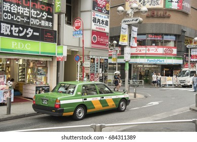 TOKYO, JAPAN, Jul 8 2017: green taxi waits at a red light and one of the streets of Shibuya district.