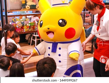 Tokyo, Japan - July 13, 2019 - Pikachu perfomance at the Pokémon Café in Nihonbashi. Someone dressed as Pikachu is entertaining the guests and shaking hands with children.