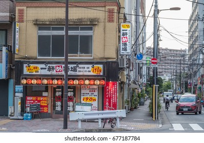 TOKYO, JAPAN - JULY 13TH, 2017. Small eateries serving the famous monjayaki dish (savoury pancake with cabbage and various fillings) in Nishinaka Street, Tsukishima, Tokyo.