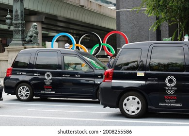 TOKYO, JAPAN - July 14, 2021: Taxis on Nihonbashi Bridge with an Olympic Ring monument and statue of a lion in the background. They are Toyota JPN taxis with Tokyo Olympic logo on them.