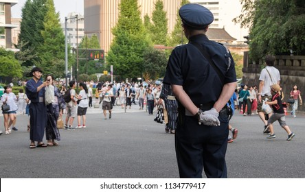 TOKYO, JAPAN - JULY 14TH, 2018. Japanese security officer on duty at Yasukuni Shrine during Mitama (or Soul) Summer Festival.