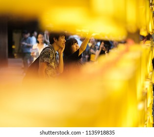 TOKYO, JAPAN - JULY 14TH, 2018. Japanese couple among the yellow lanterns at Yasukuni Shrine during Mitama (or Soul) Summer Festival.