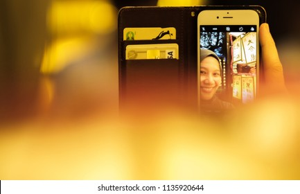 TOKYO, JAPAN - JULY 14TH, 2018. Muslim woman tourist hand holding smartphone among the rows of yellow paper lanterns at Yasukuni Shrine during Mitama (or Soul) Summer Festival.
