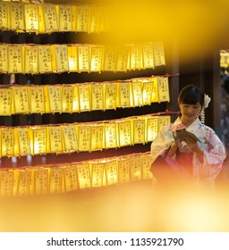 TOKYO, JAPAN - JULY 14TH, 2018. Japanese girl in traditional yukata dress among the rows of yellow paper lanterns at Yasukuni Shrine during Mitama (or Soul) Summer Festival.