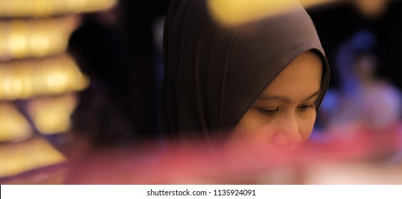TOKYO, JAPAN - JULY 14TH, 2018. Muslim woman tourist walking among the rows of yellow paper lanterns at Yasukuni Shrine during Mitama (or Soul) Summer Festival.