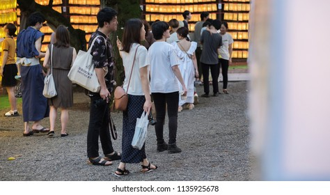 TOKYO, JAPAN - JULY 14TH, 2018. Visitors and tourist walking among the rows of yellow paper lanterns at Yasukuni Shrine during Mitama (or Soul) Summer Festival.