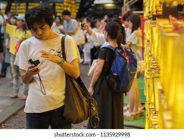 TOKYO, JAPAN - JULY 14TH, 2018. Visitors with smartphone among the yellow lanterns at Yasukuni Shrine during Mitama (or Soul) Summer Festival.