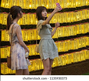 TOKYO, JAPAN - JULY 14TH, 2018. Japanese girls with smartphone among the yellow lanterns at Yasukuni Shrine during Mitama (or Soul) Summer Festival.