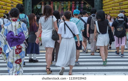TOKYO, JAPAN - JULY 14TH, 2018. Tourists crossing the road at Yasukuni Shrine during Mitama (or Soul) Summer Festival.