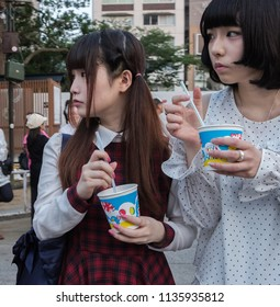 TOKYO, JAPAN - JULY 14TH, 2018. Japanese girls with food at Yasukuni Shrine during Mitama (or Soul) Summer Festival.