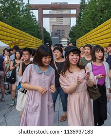 TOKYO, JAPAN - JULY 14TH, 2018. Japanese girls with smartphone at Yasukuni Shrine during Mitama (or Soul) Summer Festival.