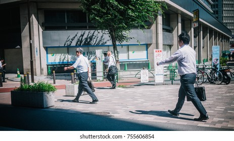 TOKYO, JAPAN - JULY 15, 2015: Japanese Men White-Collar Worker or Salaryman in Shirts Walking in Sync on the Street Heading to Office with Business Messenger Work Bags. Day time with summer sunlight.