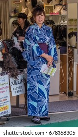 TOKYO, JAPAN - JULY 15TH, 2017.  Woman in kimono in front of her shop in Sugamo JIzodori shopping street.  Often referred to as Grandma's Harajuku, the street is very popular with elderly people.